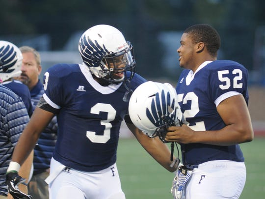 David Reese (left) offers encouragement to former teammate Courteous Preston, who now plays at Ferris State University.