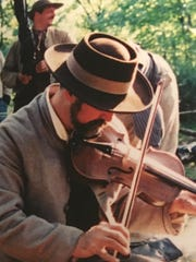 As a Civil War history buff, Dr. Frank McCutcheon, Jr. once participated in re-enactments and entertained fellow troops with his fiddle, as he did in this 1998 photo from a Battle of Gettysburg event.
