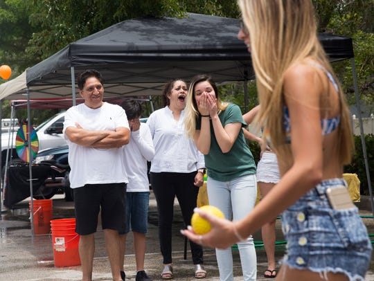 Erika Hurtado, right from center, her mother, Erika, and father, Marco, laugh during attempts made at the dunk tank Saturday, July 21, 2018, at Hooters in North Naples. Hooters was holding a fundraiser for father and son Marco and Bryan Hurtado, who work at the restaurant. A fire in their home in June displaced the Hurtado family of six. in addition to the dunk tank, there was putt putt golf, a raffle, bake sale and car wash at the fundraiser.