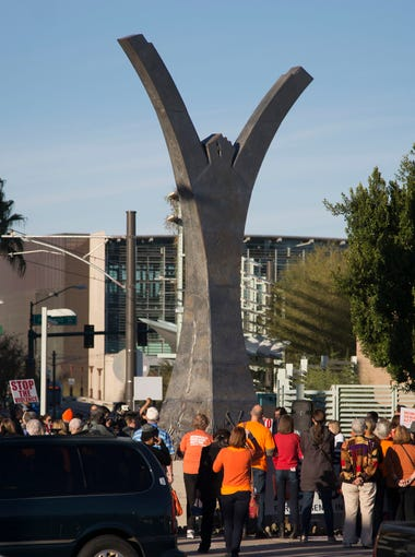 People arrive during a vigil to end gun violence after a march in downtown Phoenix on Dec. 13, 2015 in Phoenix, Ariz. The march ended at the Release the Fear Sculpture built from melted weapons used in crimes.