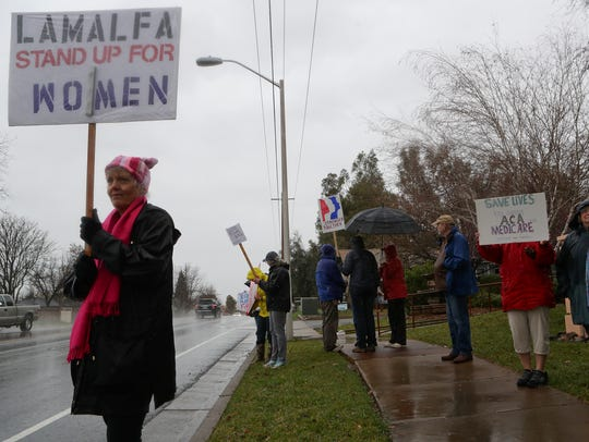 Rhonda Savoy, left, and others hold signs along Churn