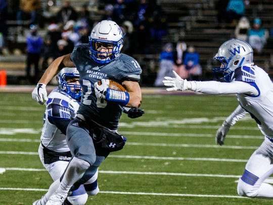 Brookfield Central running back Zach Heckman (28) breaks away from Waukesha West defenders during the Level 4 Division 2 playoff game at Oconomowoc on Friday, Nov. 10, 2017.