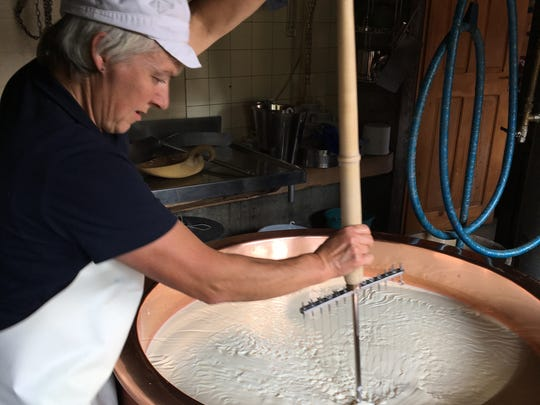 Käthy Gwerder, whose family owns Wasserberg cheese dairy in Switzerland, stirs cheese curds during the early stage of making mutschli cheese.
