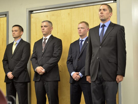 From left, newly sworn Burlington police officers David
