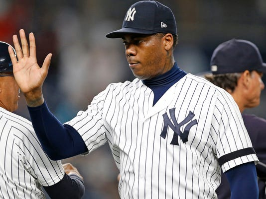 New York Yankees relief pitcher Aroldis Chapman greets teammates after earning a save in the Yankees 2-1 victory over the Minnesota Twins in New York, Monday, Sept. 18, 2017. (AP Photo/Kathy Willens)