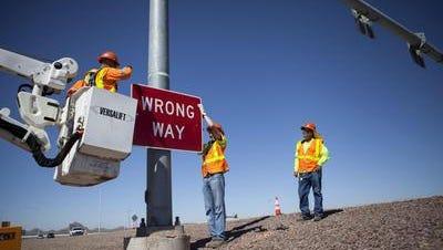 "ADOT crews hang a larger ""wrong way"" sign at the Interstate 17 interchange at Carefree Highway in Phoenix."