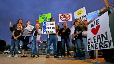 Solar energy activists demonstrate against a local tax on solar array owners