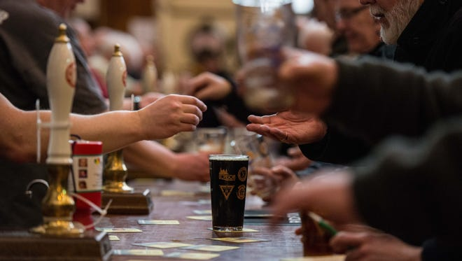 Money and beer swap hands over the bar as a pint of stout sits at the London Drinker Beer and Cider Festival at the Camden Centre on March 2, 2016, in London.