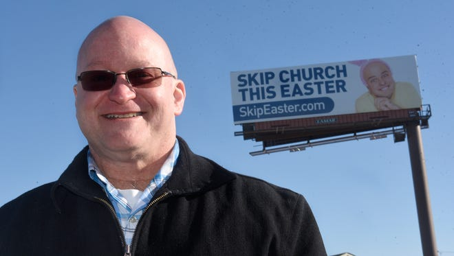 "The Rev. Scott McKee, senior pastor of Northville-based Ward Presbyterian Church, stands near a billboard along I-275 in Livonia that reads ""SKIP CHURCH THIS EASTER."""