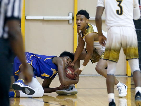 Irondequoit's Gerald Drumgoole and Greece Athena's Christian Jones wrestle for the ball in the second quarter at Greece Athena High School.