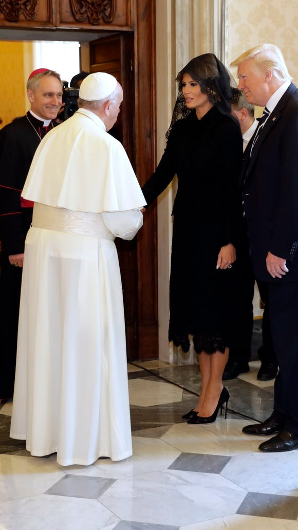 Pope Francis takes Melania's hand.