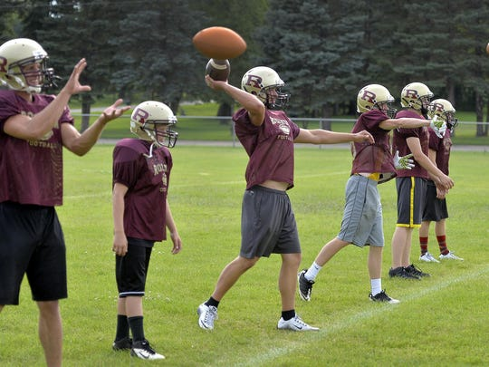 Royalton football players warm up with a passing drill