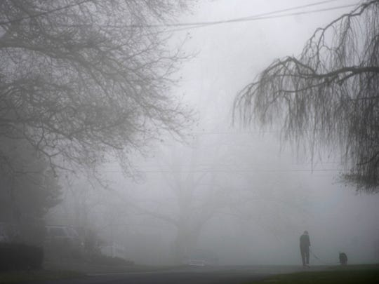 A thick fog covers this Springettsbury Township neighborhood as a dog is taken for a walk. Fog blanketed the region Christmas morning and persisted throughout the afternoon.