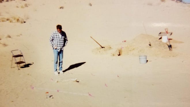 Kent Hicks, an anthropologist from Texas Tech, stands near the skeletal remains discovered by Gene Lynskey in Yoakum County in late 1997.  The site was once covered by the large dune in the background.