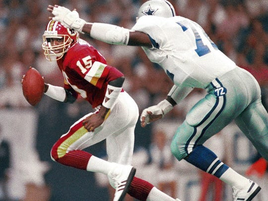 Washington Redskins quarterback Tony Robinson eludes the pass rush of the Dallas Cowboys during a game in 1987.