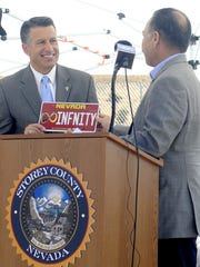 Gov. Brian Sandoval (left) accepts a vanity plate from Nevada Department of Transportation Director Rudy Malfabon.