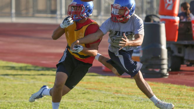 Jerry Miranda, left, and Paulino Gutierrez fight for a thrown ball during Indio High School's football practice, August 17, 2017.