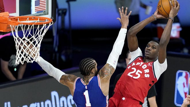Toronto's Chris Boucher, who had 19 points, shoots over Philadelphia's Mike Scott (1) during the second half of Wednesday's game in Lake Buena Vista, Fla.