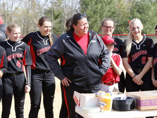Corning coach Stacy Johnson, front, is honored for recently reaching 500 career wins during a ceremony after Tuesday's 4-3 victory over Monroe Community College in Corning.