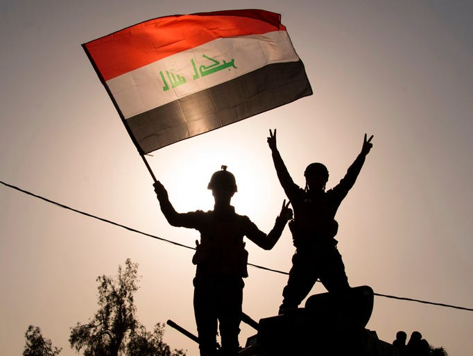 Iraq's federal police members wave Iraq's national