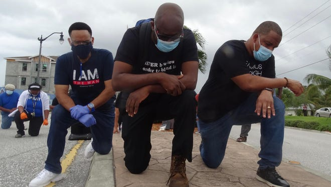 Deacon Guarn Sims, Reverend Rae Whitely and Pastor Rodney Wilkinson kneel Tuesday during a peaceful meeting in Boynton Beach.