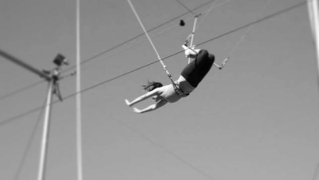 Kimberly Novosel faces her fear of heights from the bar of a trapeze.