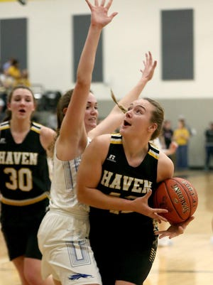 Haven's Maguire Estill (42) drives past Halstead's Karenna Gerber (5) during the 47th Annual Wildcat Classic in Haven on Friday night. Haven defeated Halstead 34 - 27.