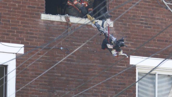 A Cincinnati firefighter discards smoldering debris from a fire.