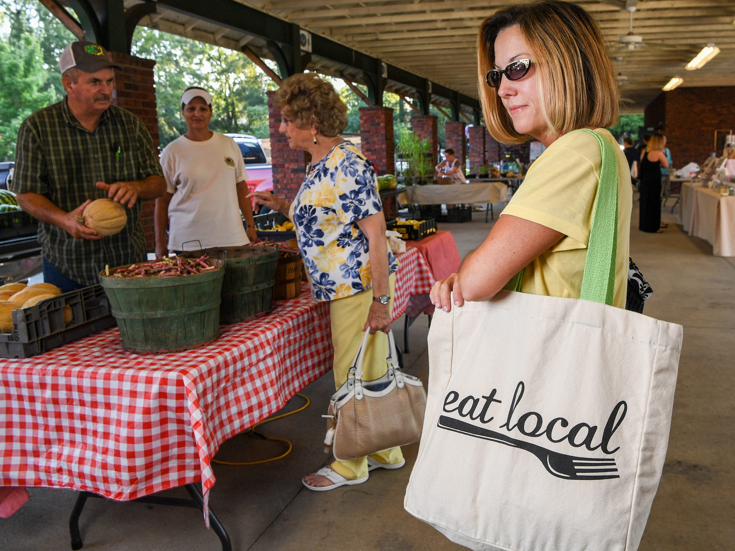 Robin Cathey of Anderson carries a cloth bag with produce