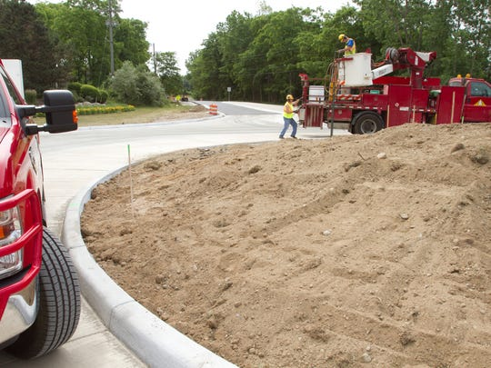 The roundabout under construction at the intersection of Chilson and Coon Lake Roads is nearing completion. Preparing to hang directional signs are Livingston County Road Commission sign directors Brad Smith (on the ground) and Dan Toles.