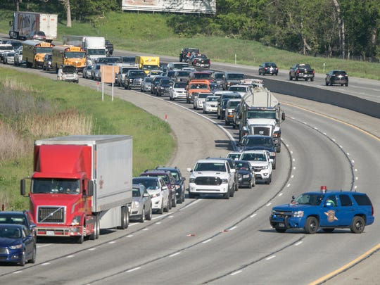 Michigan State Police divert drivers off at Kensington Road from eastbound I-96 due to an overturned double-semi truck crash near the county line Friday, May 25, 2018.