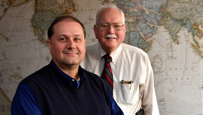 Greg Swindle, left, and Bill Brant stand before a global map in the Hope for Life offices Dec. 28, 2017. Brant has retired as president and chief executive officer of the organization, with Swindle as his relief.
