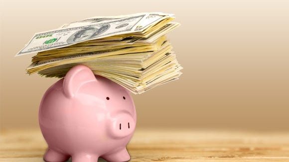 pink piggy bank with a stack of hundred dollar bills resting on top of it