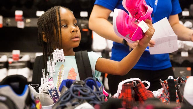 Boys & Girls Clubs of the Tennessee Valley kid Amilah Robinson, 5, picks out sneakers at Academy Sports & Outdoors in West Knoxville Wednesday, July 26, 2017. 30 boys & girls got to each go on a $100 shopping spree for back to school items at the store.