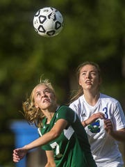 Colchester's Clara Johnson, left, and St. Johnsbury's Grace Cooke eye the ball in Colchester on Friday, September 25, 2015.