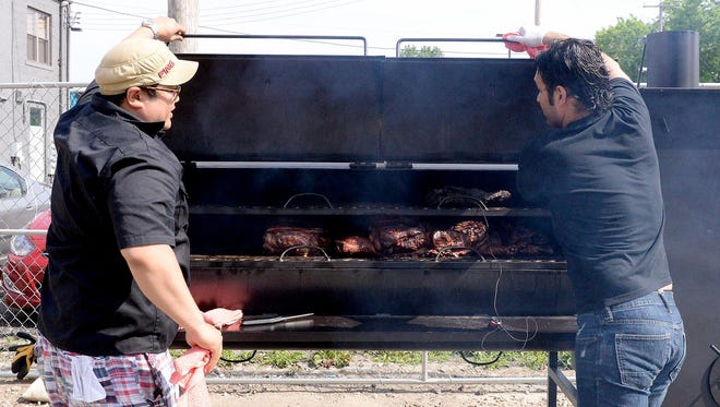 Matt Gillett and Laith Salman open up the smoker at Saddleback Barbecue June 4, 2015, behind the new restaurant in REO Town.