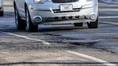 It's pothole season. Cars maneuver around the cratered pavement on E. Kalamazoo Street in Lansing on Saturday, Jan. 20, 2018.
