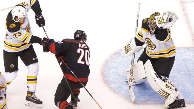Boston Bruins' goaltender Jaroslav Halak (41) makes a save as Bruins' Charlie McAvoy (73) battles with Carolina Hurricanes' Sebastian Aho (20) during the second period of a NHL Eastern Conference Stanley Cup playoff game in Toronto, on Saturday, Aug. 15, 2020.