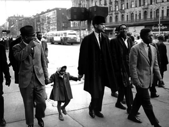 Malcolm X holds the hand of his daughter, Ilyasah Shabazz, as they walk down the street, undated photo.