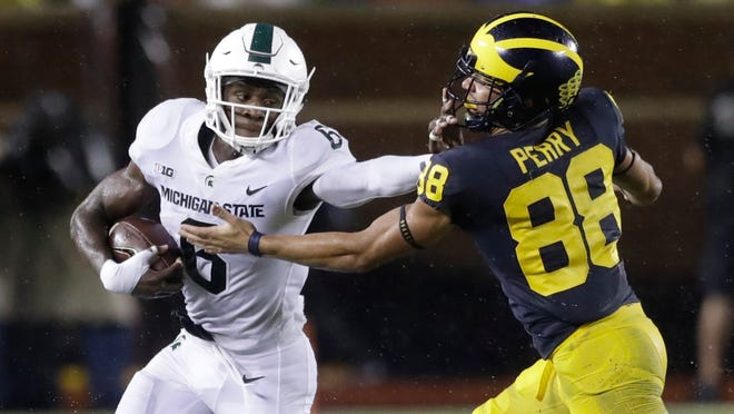 Michigan State safety David Dowell (6) stiff arms Michigan wide receiver Grant Perry (88) after intercepting a pass during the second half of an NCAA college football game, Saturday, Oct. 7, 2017, in Ann Arbor, Mich. (AP Photo/Carlos Osorio)