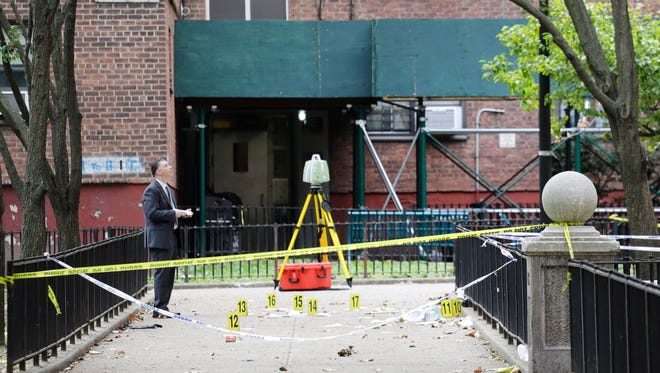 A New York City crime scene investigator inspects the scene of a triple homicide, Sunday, Sept. 20, 2015 at the Ingersoll Houses in Brooklyn after three men were killed there early Sunday.