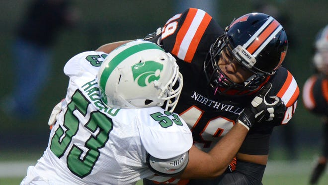 Northville Mustang Ryan Roberts, right, and Novi Wildcat Joey Haddad go to battle against each other during their teams' annual big rivalry game on Oct. 10, 2014.