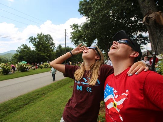 Seacrest Country Day School 10th-graders Olivia Westervelt, 15, left, and Thomas Richardson, 15, watch the solar eclipse in Dillard, Ga., Monday, Aug. 21, 2017.