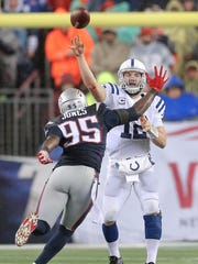 Indianapolis Colts quarterback Andrew Luck (12) gets rid of a pass in the heat of a defensive rush from New England Patriots defensive end Chandler Jones (95) during last year's AFC Championship game.