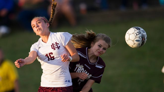 Henderson County's Katie Bickers (16) heads the ball past Webster County's Brooke Clark (21) during the Sixth District championship game at Union County High School in Morganfield,  Tuesday, Oct. 11, 2016. Henderson County beat Webster County 11-1.