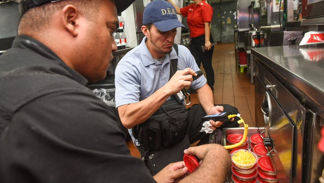 During a routine health inspection, Environmental Public Health Officers Evan Lum, right, uses a digital probe to ensure the proper food temperature is maintained within a heated storage bin as Restaurant Manager Perry Yalolmar observes at the KFC fast-food restaurant in Tamuning on Tuesday, Sept. 19, 2017.
