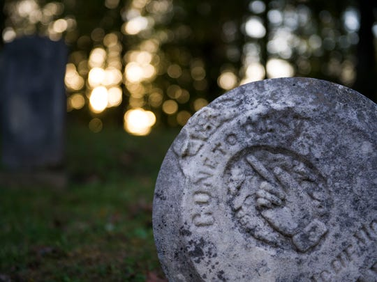 """A grave stone station """"Gone to rest""""  sits in the cemetery"""
