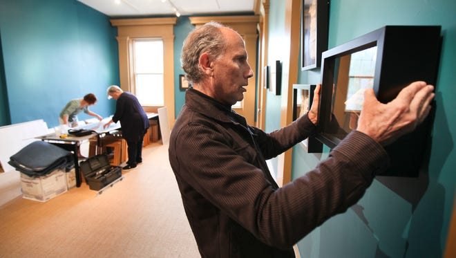 Artist Julius Friedman hangs a shadow box at the Portland Museum. Friedman will exhibit work created from books at the museum.