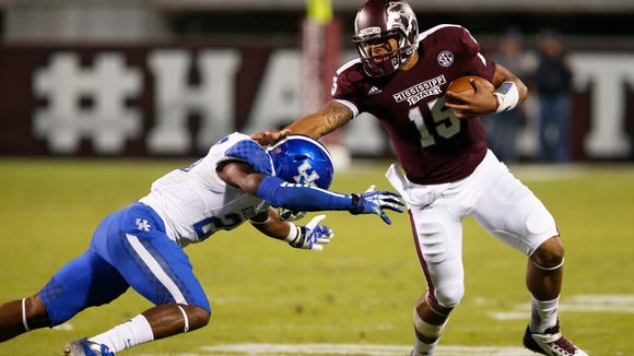 Mississippi State quarterback Dak Prescott (15) fights off a tackle attempt by Kentucky safety Eric Dixon (28) as he runs for long yards in the first half of their NCAA college football game at Davis Wade Stadium in Starkville, Miss., Thursday, Oct. 24, 2013. (AP Photo/Rogelio V. Solis)