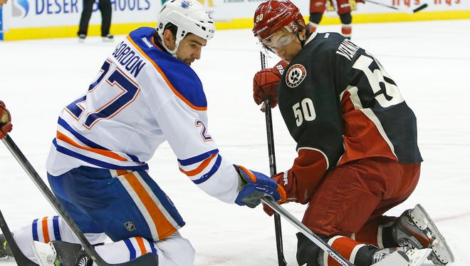Edmonton Oilers center Boyd Gordon (27) and Phoenix Coyotes center Antoine Vermette (50) fight for the puck following a face off during the second period of their NHL game Tuesday, Dec. 31,, 2013 in Glendale.